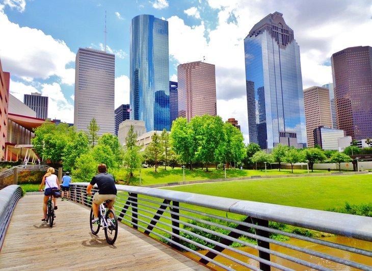 Bicyclists cross wooden bridge Buffalo Bayou Park view downtown Houston